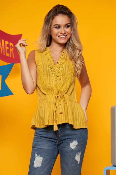 Yellow casual flared women`s blouse slightly transparent fabric is fastened around the waist with a ribbon with lace details